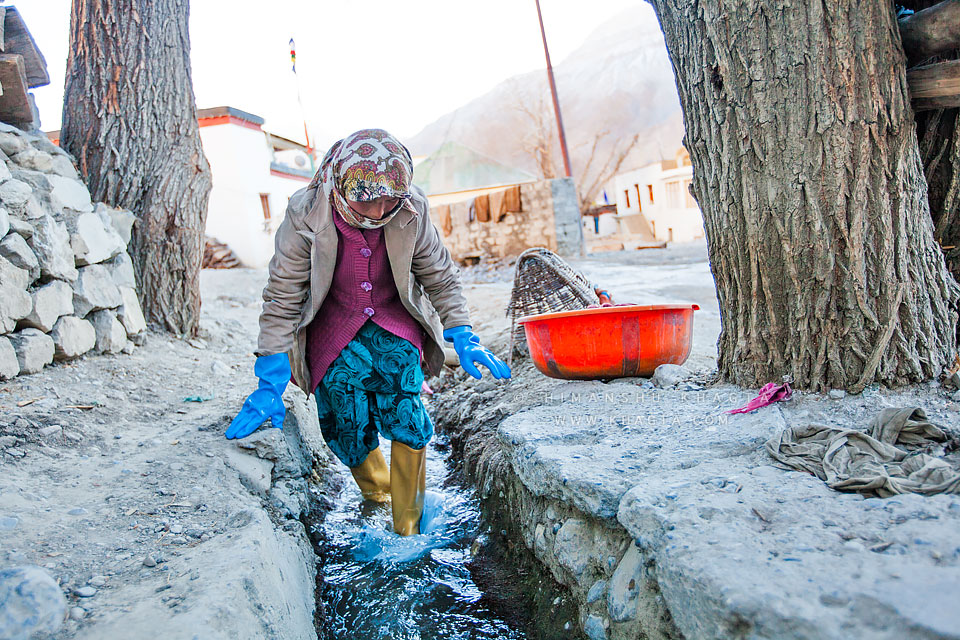A Lady washing clothes after work in an irrigation canal that passes through Kaza village in Spiti